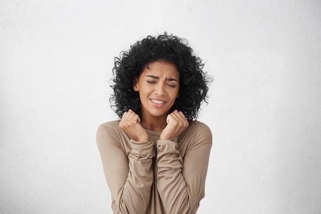 Портрет ликующей и жизнерадостной счастливой молодой темнокожей женщины, подняв талию вверх, радуется от волнения