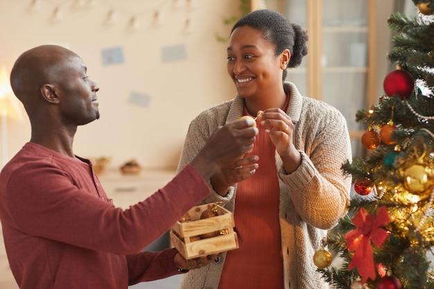 家でホリデーシーズンを楽しみながら一緒にクリスマスツリーを飾る愛するアフリカ系アメリカ人のカップルの肖像画を腰に当てる