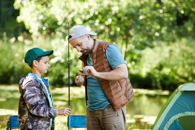 Портрет любящего отца, поднимающего талию, учит сына настраивать рыболовное снаряжение, наслаждаясь вместе в походе, копировальное пространство