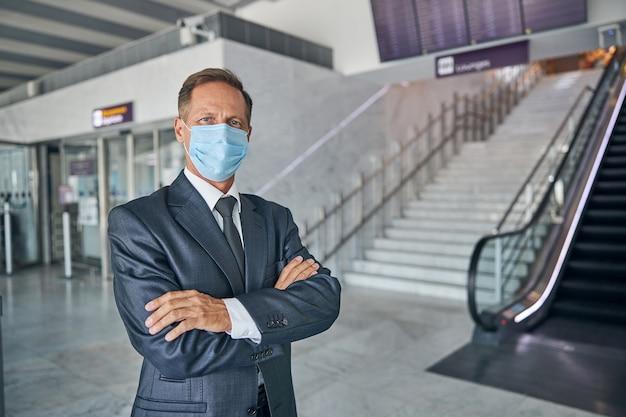 전염병 동안 출발하기 전에 공항 홀에 서 있는 우아한 정장을 입은 남성의 허리 초상화