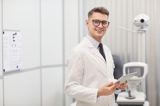 カメラに微笑んでいる男性の検眼医の肖像画をウエストアップ