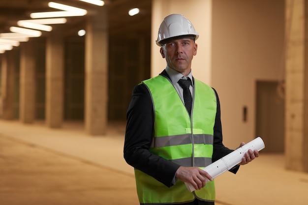 안전모를 착용하고 실내 건설 현장에 서있는 동안 성숙한 사업가의 초상화를 허리 위로,