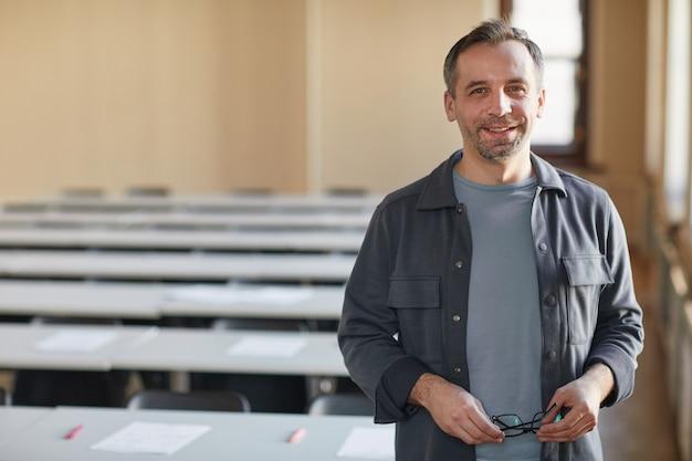 학교 강당에 서 있는 동안 카메라를 보며 웃고 있는 성숙한 대학 교수의 허리 초상화, 복사 공간