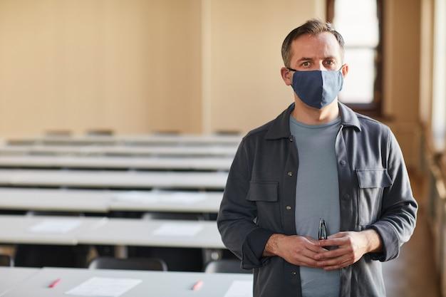 학교 강당에 서서 카메라를 보고 공간을 복사하는 동안 마스크를 쓴 성숙한 대학 교수의 허리 초상화