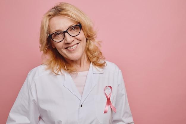 스튜디오에서 분홍색 배경에 포즈를 취하는 동안 카메라에 미소 흰색 코트에 핑크 리본으로 성숙한 여성 의사의 초상화를 허리, 복사 공간