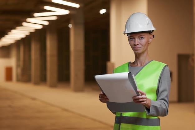 안전모를 착용하고 실내 건설 현장에 서있는 동안 성숙한 여성 노동자의 초상화를 허리 위로,