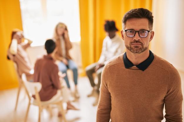 지원 그룹에서 치료 세션 동안 카메라를 보고 있는 성숙한 남성 심리학자의 허리 초상화, 복사 공간
