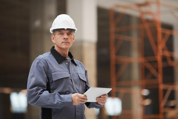 디지털 태블릿을 들고 건설 현장이나 산업 작업장에 서있는 동안 성숙한 노동자의 초상화를 허리 위로 올리십시오.