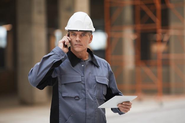 스마트 폰으로 말하고 건설 현장이나 산업 작업장에 서있는 동안 성숙한 노동자의 초상화를 허리 위로 올리고,
