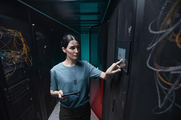 Поднимите талию портрет военной женщины, использующей панель управления при настройке серверов в центре обработки данных, скопируйте пространство