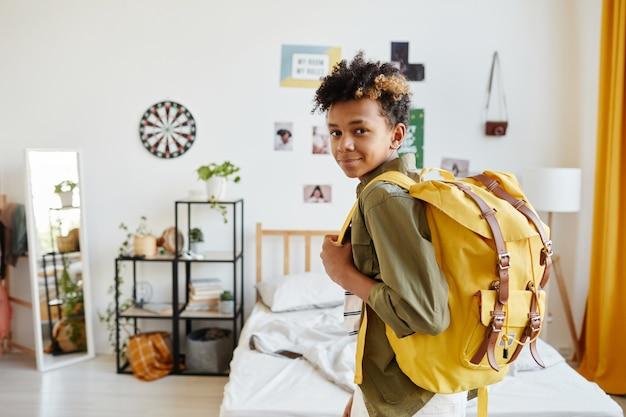 배낭을 들고 학교에 갈 준비를 하는 동안 카메라를 보며 웃고 있는 혼혈 10대 소년의 허리 초상화, 복사 공간