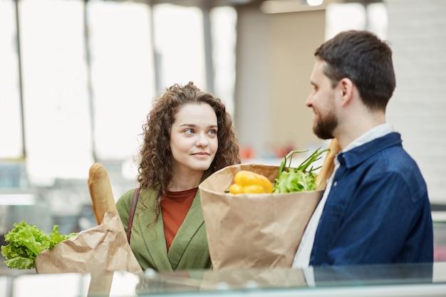 Талия вверх портрет современной взрослой пары, держащей бумажные пакеты с продуктами, наслаждаясь покупками в супермаркете