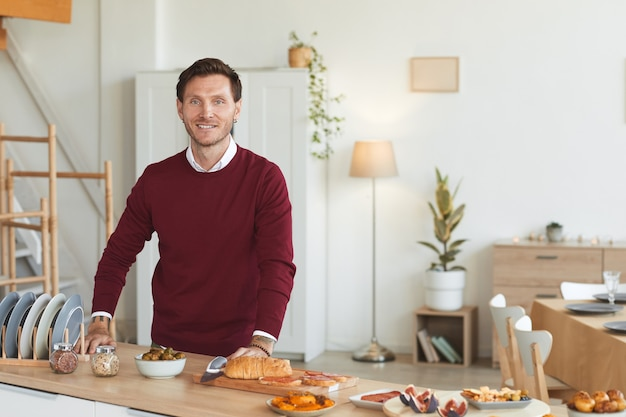 現代の大人の男性の肖像画を腰に上げ、屋内でディナーパーティーのために料理をしながら笑っています。