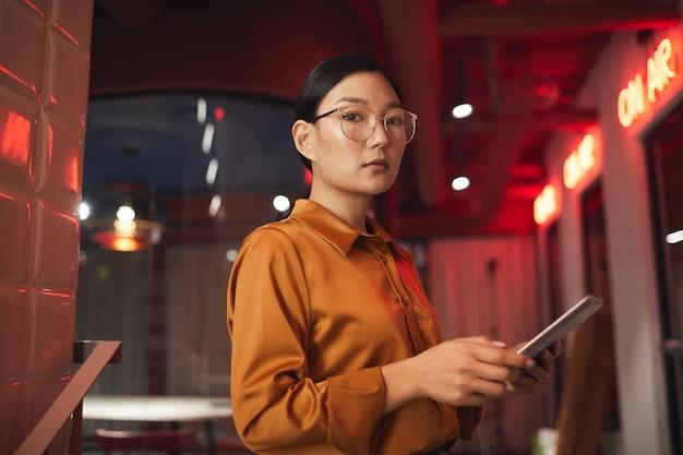 Талия вверх портрет современной азиатской бизнес-леди, держащей планшет и позирующей на открытом воздухе