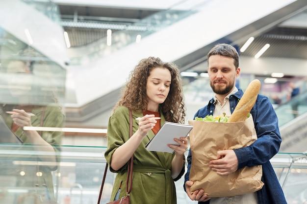 スーパーマーケットで食料品を購入しながら買い物リストをチェックする現代のカップルの肖像画を腰に当てる