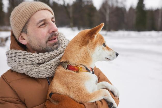 Талия вверх портрет современного зрелого мужчины, держащего собаку и смотрящего в сторону, наслаждаясь прогулкой в зимнем лесу, копией пространства
