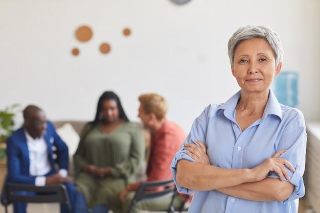 자신있게 포즈를 취하는 현대 성숙한 여자의 초상화를 허리, 그룹 리더 개념, 복사 공간에 동그라미에 앉아있는 사람들과 함께