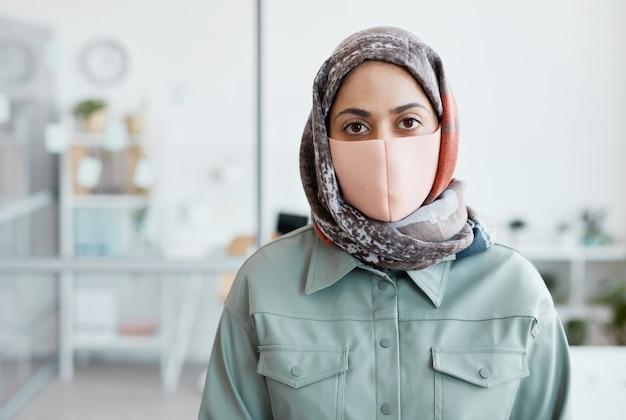 사무실 내부에 서 있는 동안 마스크를 쓰고 카메라를 바라보는 현대 중동 여성의 허리 초상화, 복사 공간