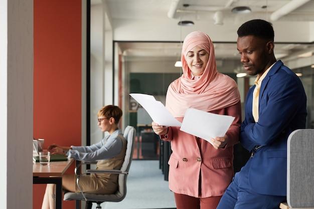 アフリカ系アメリカ人の同僚と話し、オフィスのインテリア、コピースペースに立っている間に文書について話し合う現代のイスラム教徒の実業家の肖像画を腰に当てる