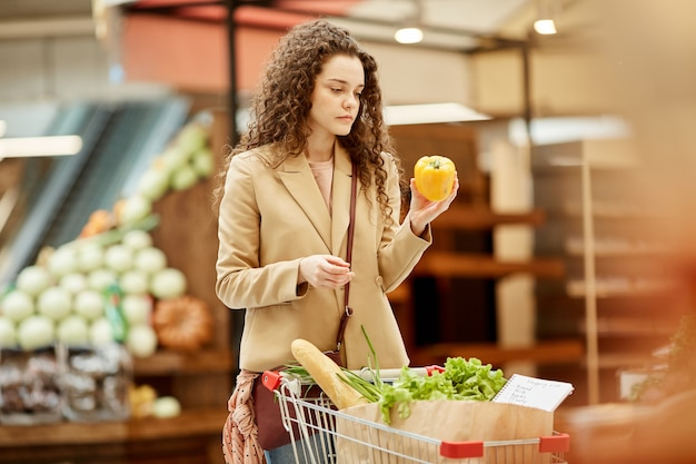ファーマーズマーケットで新鮮な果物や野菜を選択しながらピーマンを保持している現代の若い女性の肖像画を腰に当てる