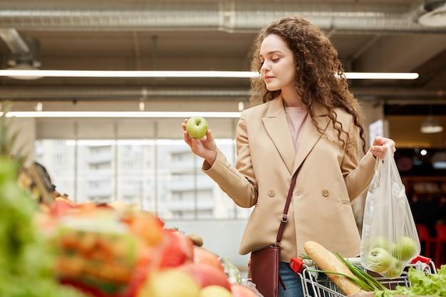 ファーマーズマーケットで新鮮な果物や野菜を選択しながら青リンゴを保持している現代の若い女性の肖像画を腰に当てる