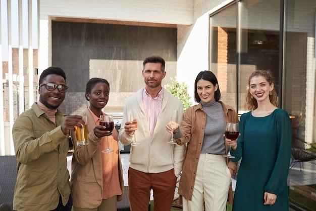 パーティー中に屋外テラスで立っているワインを楽しみながら、友人の多民族グループの肖像画を腰に当てる