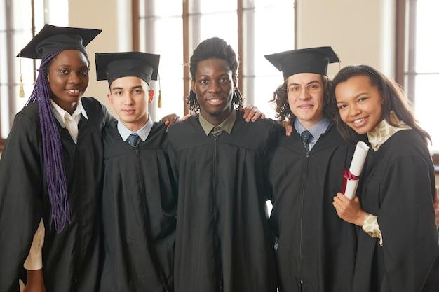 졸업 가운을 입고 학교 강당에 서 있는 동안 카메라를 보며 웃고 있는 다민족 젊은이들의 허리 위 초상화