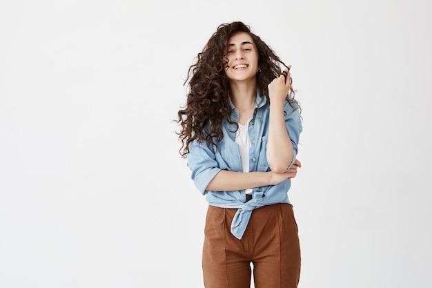 Талия-вверх портрет положительной эмоциональной темноволосой девушки широко носит джинсовую рубашку, играет с волнистыми волосами, радуется жизни, демонстрирует белые зубы. красота, счастье и молодость