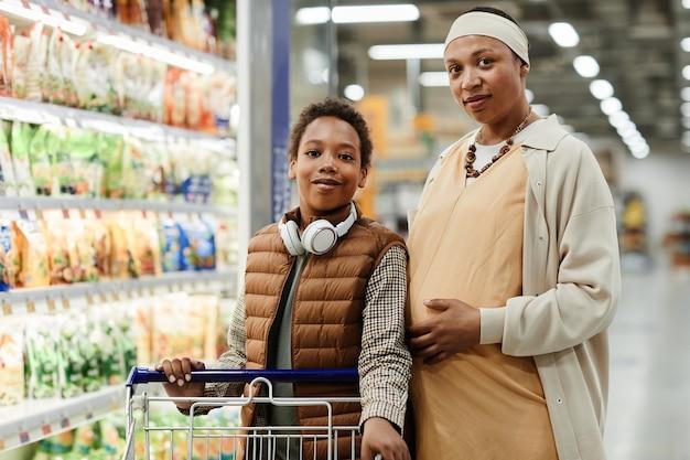 Талия вверх портрет беременной афро-американской женщины, позирующей в продуктовом магазине с сыном-подростком и смотрящей в камеру