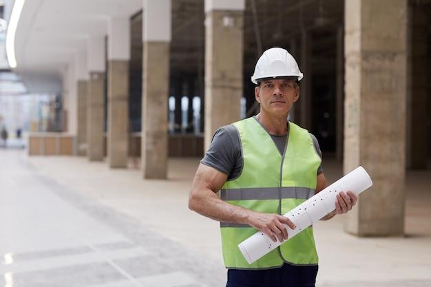 계획을 들고 사무실 건물에 서있는 동안 전문 건설 노동자의 초상화를 허리 위로,