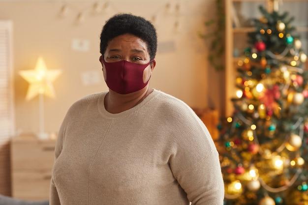 마스크를 착용하고 크리스마스를 축하하는 동안 카메라를보고 수석 아프리카 계 미국인 여자의 초상화를 허리, 복사 공간