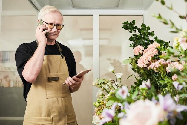 Поднимите талию портрет старшего мужчины, занимающегося инвентаризацией запасов во время работы в цветочном магазине, ко ...