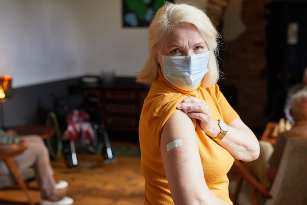 Covid 19 예방 접종 후 카메라에 어깨를 보여주는 마스크를 쓴 노인 여성의 허리 위 초상화