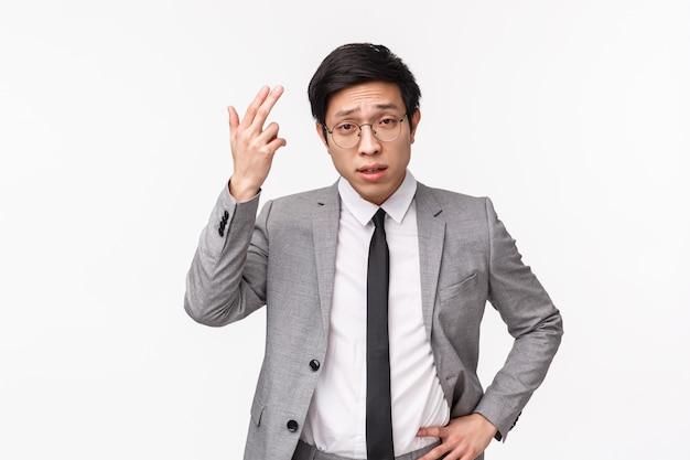 深刻な見た目で失望した若いアジア系のビジネスマンが上半身を上に向けて不平を言っている
