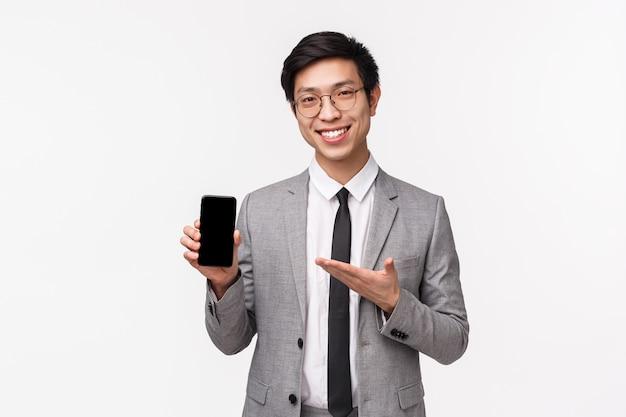 Талия-вверх портрет умного и талантливого азиатского бизнесмена представляет новое приложение для смартфонов на совещании, держит мобильный телефон, указывает на дисплей гаджета, улыбается, рекомендует скачать