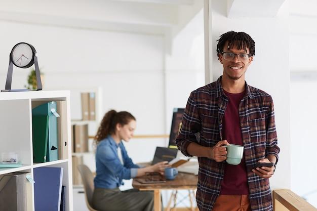 찻잔을 들고 현대 사무실 인테리어에 벽에 서있는 동안 카메라를보고 웃는 아프리카 계 미국인 남자의 초상화를 허리, 복사 공간