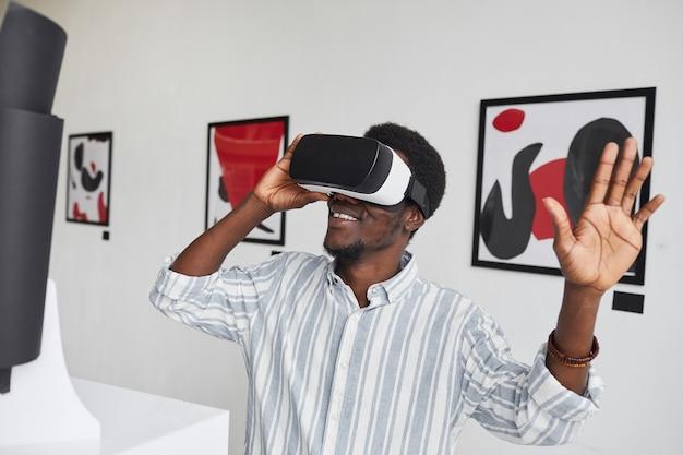 Портрет улыбающегося афроамериканца в снаряжении виртуальной реальности с завышенной талией, наслаждающегося иммерсивным опытом на выставке в галерее современного искусства