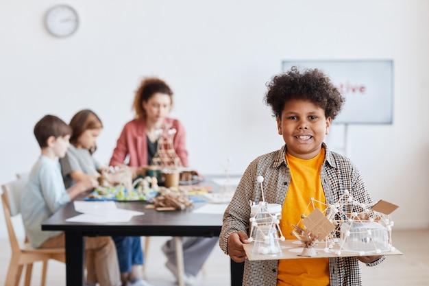木製のモデルを保持し、学校でのアートとクラフトのクラス中にカメラを見ている笑顔のアフリカ系アメリカ人の男子生徒の肖像画を腰に、コピースペース