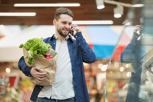スーパーマーケットで食料品の買い物をしながらスマートフォンで呼び出す笑顔のひげを生やした男の肖像画をウエストアップ