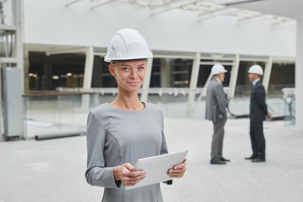 안전모를 착용하고 실내 건설 현장에 서있는 동안 태블릿을 들고 웃는 사업가의 초상화를 허리 위로,