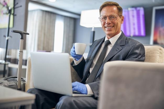 空港でラテックス手袋でコーヒーを飲みながらノートブックを使用して笑顔のエレガントなビジネスマンの肖像画をウエストアップ