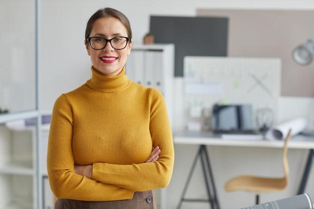 팔을 교차 하 고 사무실에서 직장에서 포즈를 취하는 동안 서 웃는 여성 건축가의 초상화를 허리,