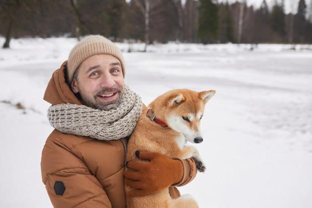 Талия вверх портрет улыбающегося зрелого мужчины, держащего собаку и смотрящего в камеру, наслаждаясь прогулкой в зимнем лесу, копией пространства