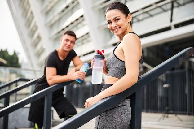 スタジアムでのトレーニング後に通信するボトルと笑顔のスリムな女性と運動選手の肖像画を腰に当てる