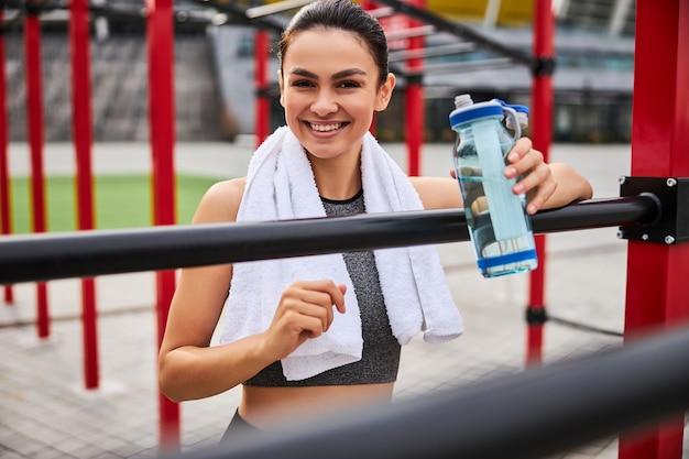 Талия вверх портрет улыбающейся спортивной девушки с бутылкой воды, стоящей на боксерском ринге на открытом воздухе