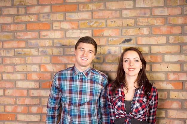 レンガの壁の前に一緒に立っている格子縞のシャツを着て笑顔の若いカップルの腰の肖像画