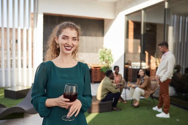 Талия вверх портрет улыбающейся молодой женщины, держащей бокал и наслаждающейся вечеринкой на открытом воздухе