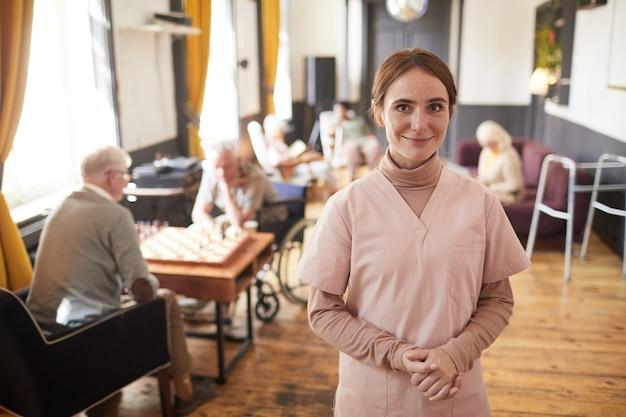 ナーシングホームのコピースペースで制服を着て笑顔の若い女性の腰の肖像画