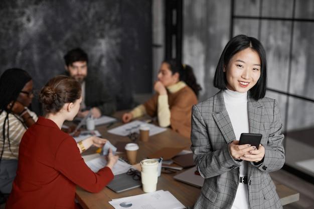Талия вверх портрет успешной азиатской бизнес-леди, улыбающейся в камеру с разнообразной группой людей, встречающихся в фоновом режиме, копией пространства