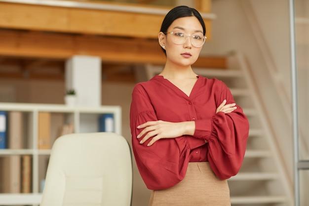 현대 사무실에서 포즈를 취하는 동안 팔을 넘어 서 성공적인 아시아 여자의 초상화를 허리, 복사 공간